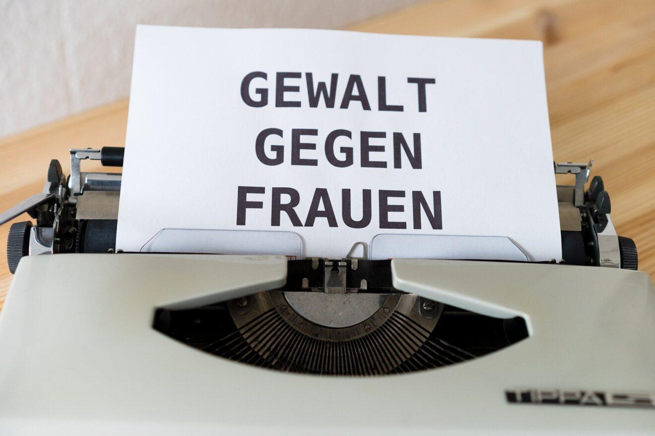 Das Foto zeigt eine Schreibmaschine mit einem eingespannten Blatt Papier, auf dem in Großbuchstaben steht: Gewalt gegen Frauen